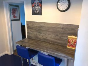 laminate worktop with splash back and two blue bar stools
