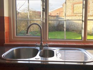 old kitchen, old sink and tap in front of window
