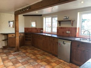 old kitchen, exposed beam, wood cabinetry, view facing the dishwasher and back wall