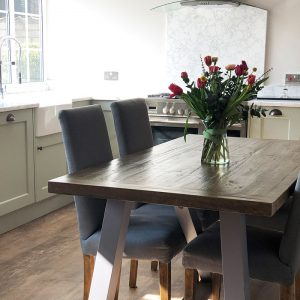 new kitchen, gorgeous flowers on the table, vintage lighting, wooden flooring, wooden table, upclose